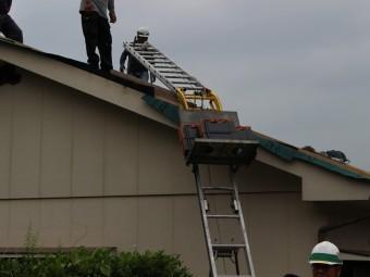 はしごで瓦を上げる